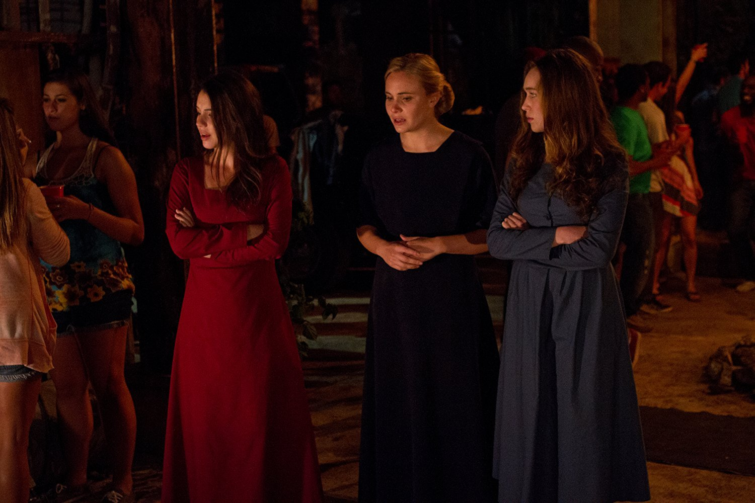 Amish girls at the party. Adelaine Kane (in a red dress) as Ruth and Alycia Debnam-Carey (in a blue dress) as Mary